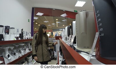 Young woman select kettle in electronics store.