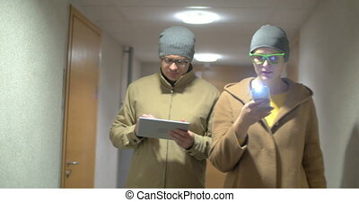 Hipster friends with pad and cell walking in hotel hall -...