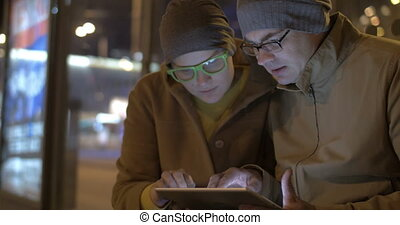 Tourists Waiting for a Bus with Tablet PC - Two tourists are...