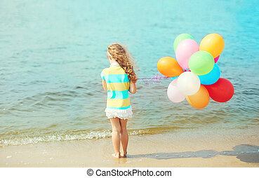 Little girl child with balloons standing on beach near sea, view back
