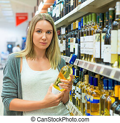 Woman choosing wine in alcohol store.