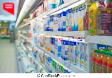 Blurred shelves with milk products in the store. Suitable...