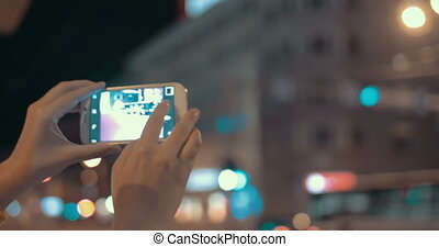 Girl with cell phone making photos of evening city - Woman...