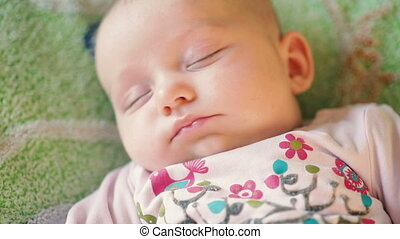 precious newborn baby is laying on a comfortable bed,...