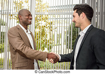 Black businessman shaking hands with a caucasian one