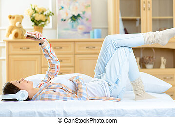 Teenage girl lying in bed and listening to music - Musical...