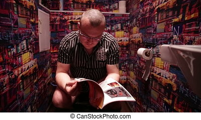 A man sitting on the toilet and read magazine