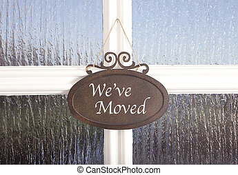 We've moved - a sign on a door with the text we have moved