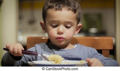 little boy eating soup