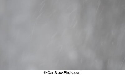 Close-up of snow falling on blurred background - Close-up of...