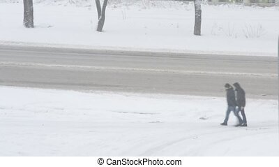 Two unidentifiable men walking along the road in snow - Two...