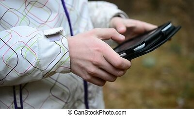 Close-up of Caucasian teenager using tablet outdoors in...
