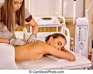 Woman receiving electricity gloves massage at beauty salon.