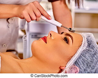 Young woman receiving electric facial massage - Woman...