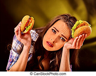 Girl eating big sandwich. - Upset girl holding big wo small...