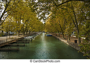 Riverside in Annecy canal - Pier and yellow trees at the...