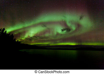 Aurora borealis swirls dancing over Lake Laberge Yukon...