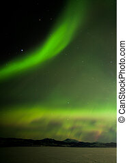 Aurora borealis dancing over frozen Lake Laberge Yukon...