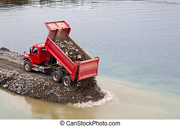 Red dump truck unloading earth fill - Red dump truck dumping...