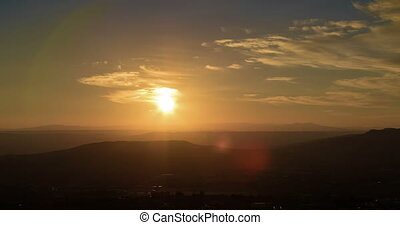 sunset scene with mountains in background time lapse,...