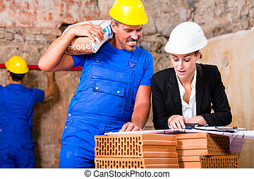 Architect and construction worker on site with plan