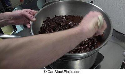 Preparation of a Yule log - melting dark chocolate over a...