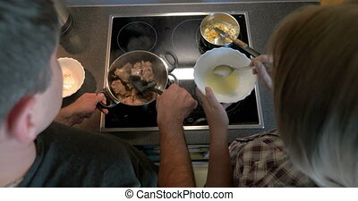 Couple cooking together meat and sauce - Top view of young...
