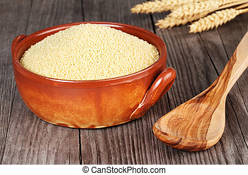 couscous in an earthenware bowl and wooden spoon