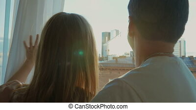 Young couple enjoying city view through the window - Back...
