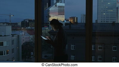 Woman Typing in Tablet by the Window - Young woman is...
