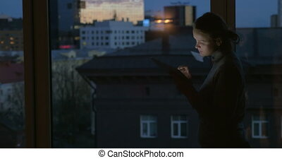 Girl working with pad by the window at night