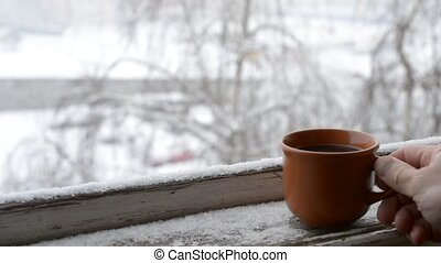 Male hand putting cup of coffee on old snow covered window...