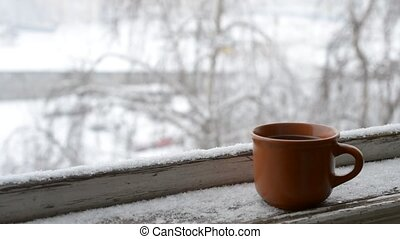 Cup of coffee on old window sill on background of falling...