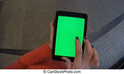 Woman at shop using tablet with green screen