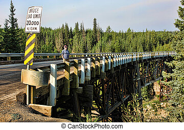 Wooden trestle bridge over a river in the Yukon