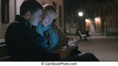 Couple Sitting on the Bench with Tablet - Young couple is...