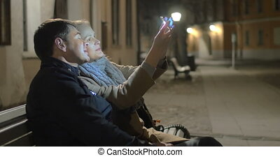 Happy couple making selfie in evening street - Happy couple...