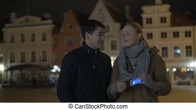 Happy couple making phone selfie in the evening street -...