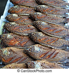 fried nile tilapia or oreochromis nilotica fish at street...
