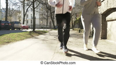Couple Jogging in Tallinn Streets - Steadicam shot of a...