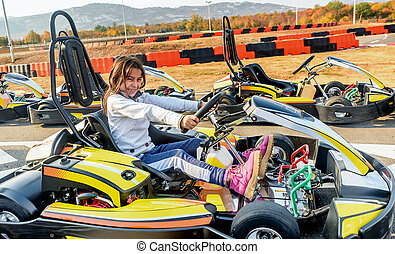 Little girl is driving Go- Kart car in a playground racing...