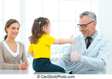 Aged doctor with little patient in hospital office -...