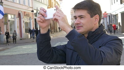 Man with smartphone making shots of buildings - Young male...