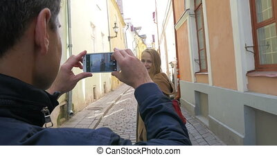 Man making photo of a woman with cell phone
