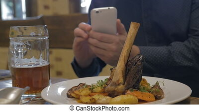 Man with phone making photo of a served dish - Man using...