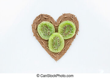 Kiwi  lies at the heart made of burlap on a white background