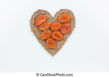 Dried apricots lies at the heart made of burlap on a white...