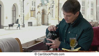 Man cleaning camera lens in outdoor cafe