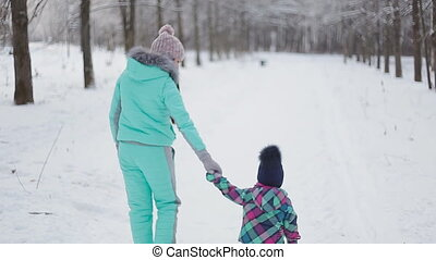 Mom and her pretty daughter in the winter walk