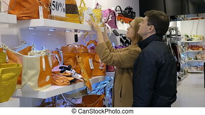 Couple choosing a handbag in the shop - Young man and woman...